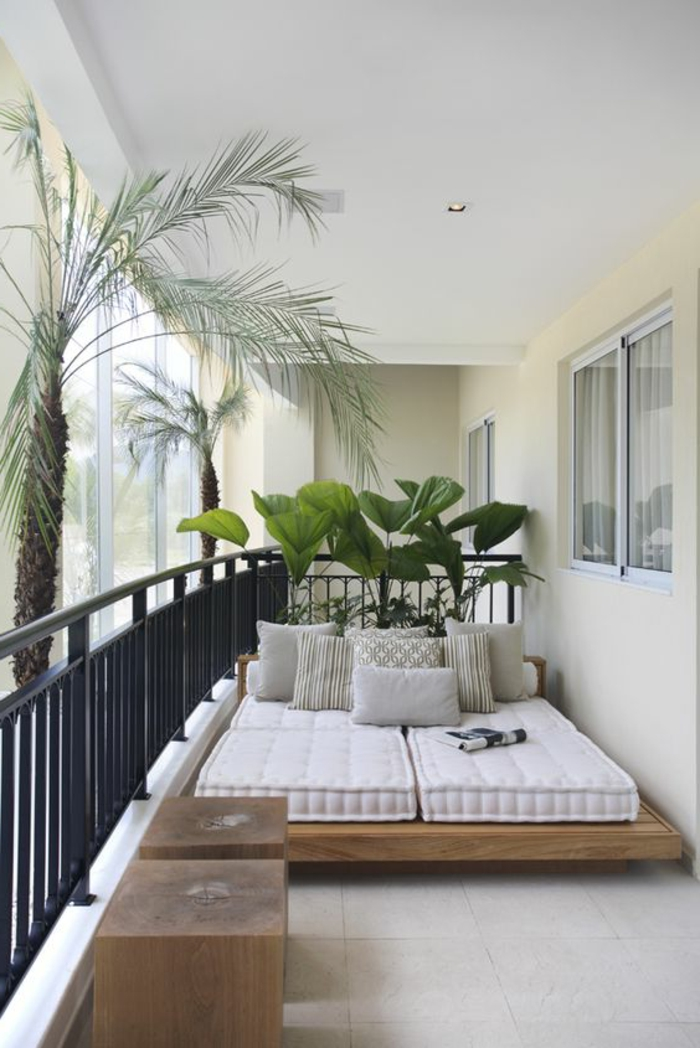 ideas-para-decorar-el-balcon-cama-con-cojines-dos-mesas-de-madera