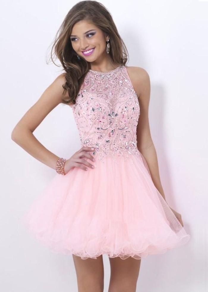 Elegante pero sencillo vestido de fiesta corto para boda o comunión, realizado en gasa de color rosa palo. Parte superior plisada con detalles en los hombros y falda lisa entallada. Preciosa espalda semidescubierta con plisado a modo de capa.