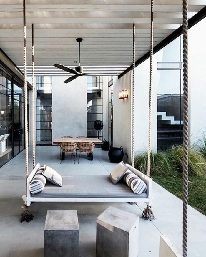 casa-minimalista-cama-colgante-mesa-y-sillas-de-madera-tonos-frios-muchas-ventanas
