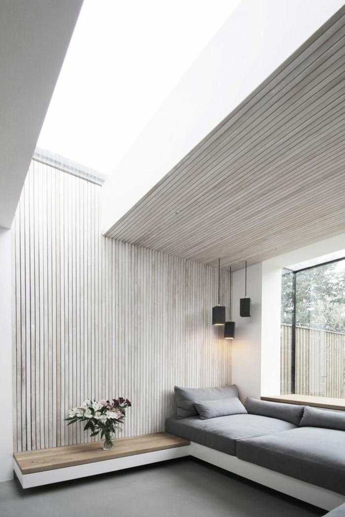 casa-minimalista-pared-de-madera-sofá-gris-grande-ventana-jarron-con-flores