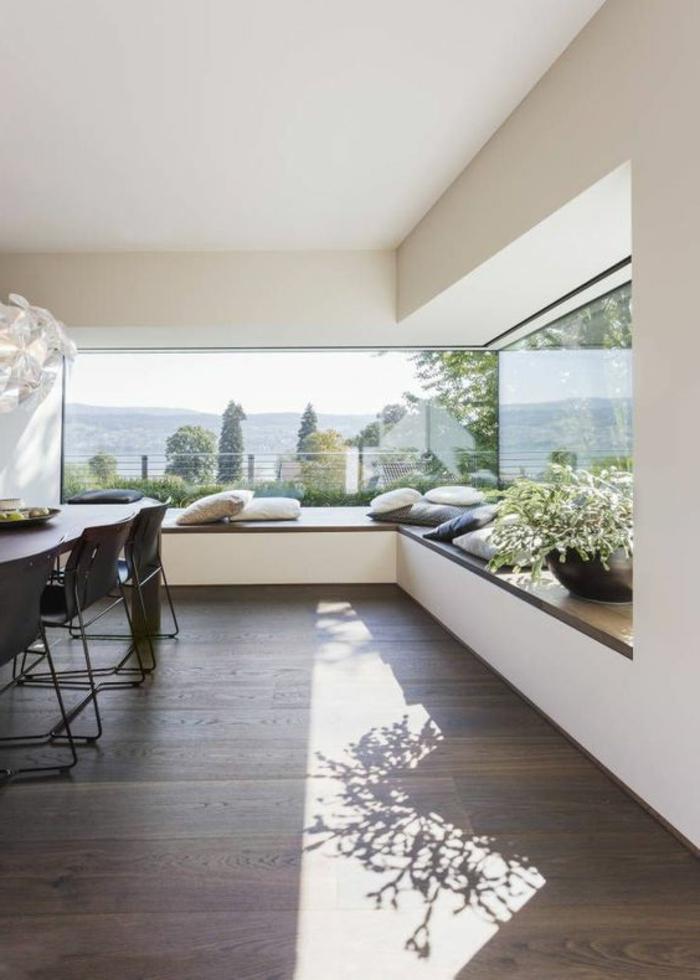 casa-minimalista-suelo-de-madera-ventanas-grandes-muchos-cojines-mesa-de-madera-sillas-de-metal