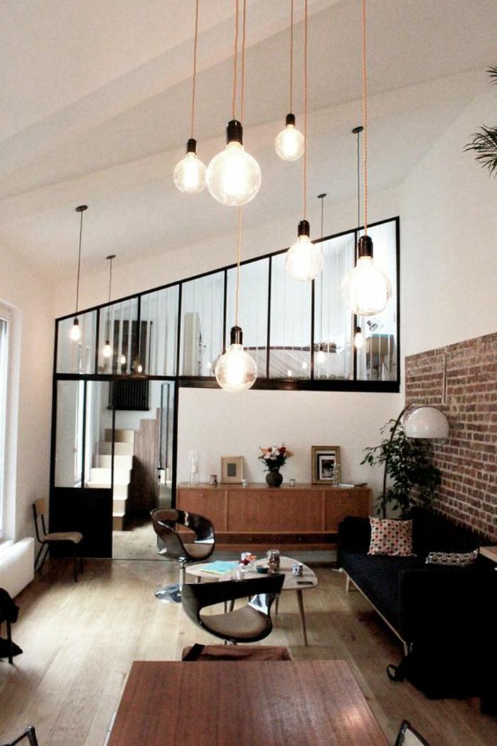 casas-minimalistas-sofa-en-negro-pared-con-ladrillos-lámparas-colgantes