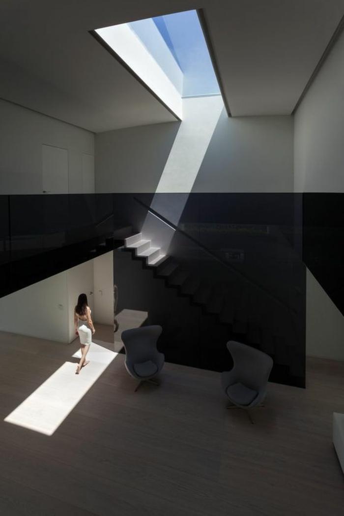 decoracion-minimalista-dos-pisos-techo-con-ventana-dos-sillones-grises-escalera