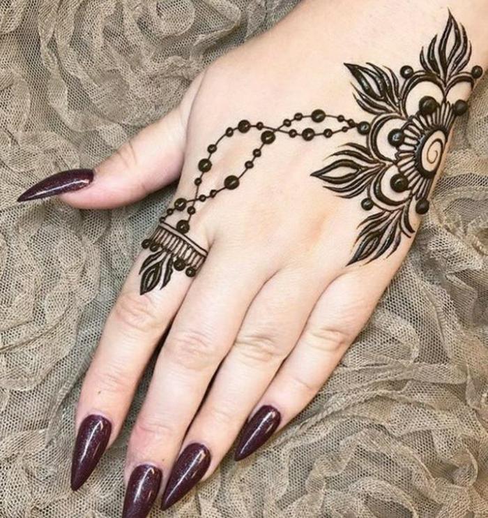 henna-tatuaje-diseño-simple-de-flor-sobre-la-mano-de-mujer