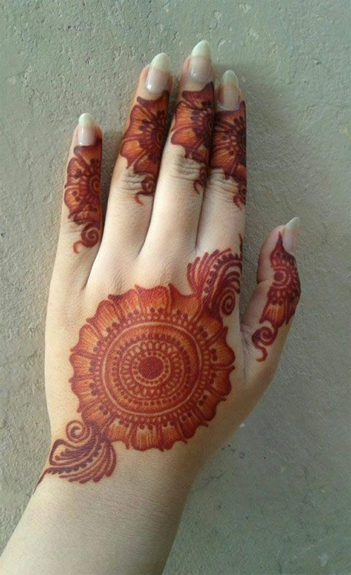 tatuajes-de-henna-roja-mandala-y-flor-en-el-mano-mujer