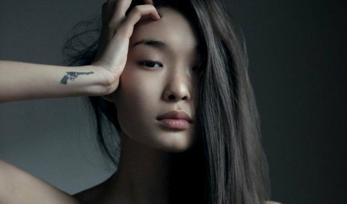tatuajes-pequeños-mujer-con-pelo-largo-y-liso-tatuaje-de-pistola-en-la-muñeca