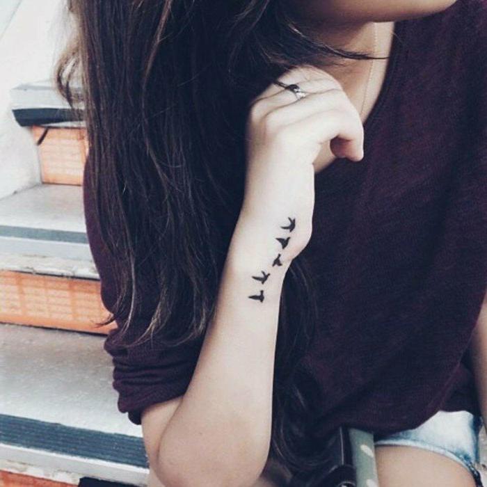 tatuajes-pequeños-mujer-pajaros-en-la-mano-bonito-femenino-mujer-con-pelo-largo