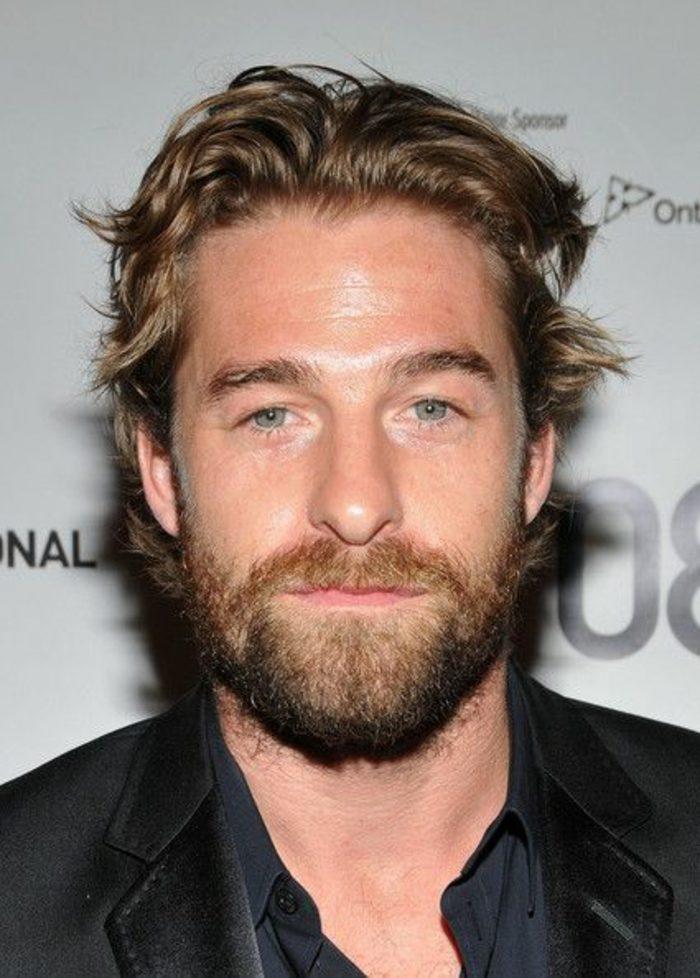 barbas-de-moda-hombre-con-ojos-azules-pelo-rubio-actor-traje-negro-elegante