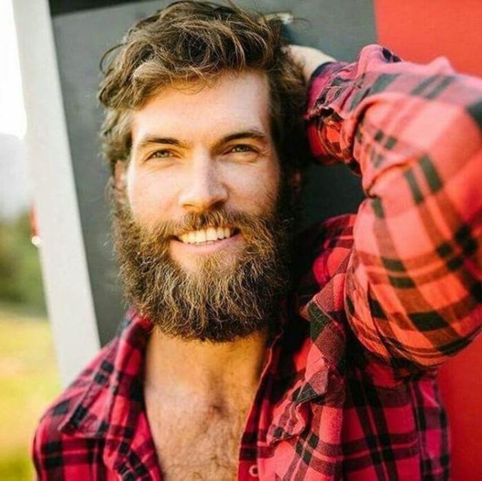 barbas-de-moda-hombre-hojos-azules-camiseta-roja-barba-larga-pelo-ondulado