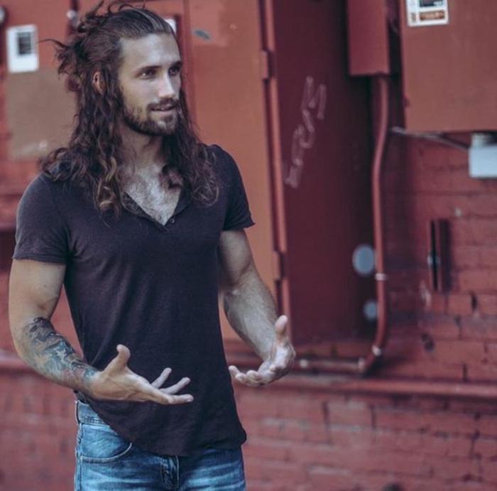 tipos-de-barba-hombre-con-pelo-largo-rizado-camiseta-tatuajes-barba-a-la-moda
