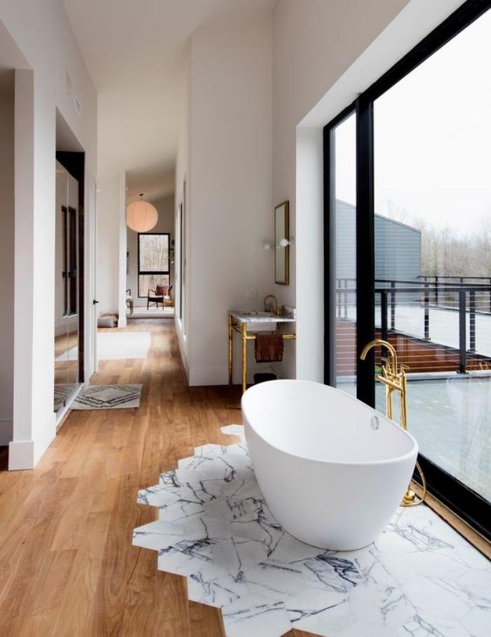 cuartos de baño pequeños, elementos dorados, ventana enorme, suelo de madera,
