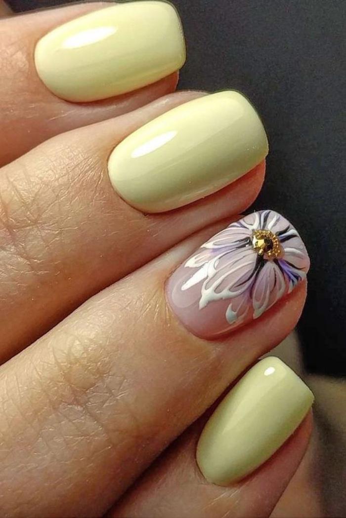 uñas pintadas, color amarillo suave, muy elegante e interesante, dibujo de flor en el dedo anular