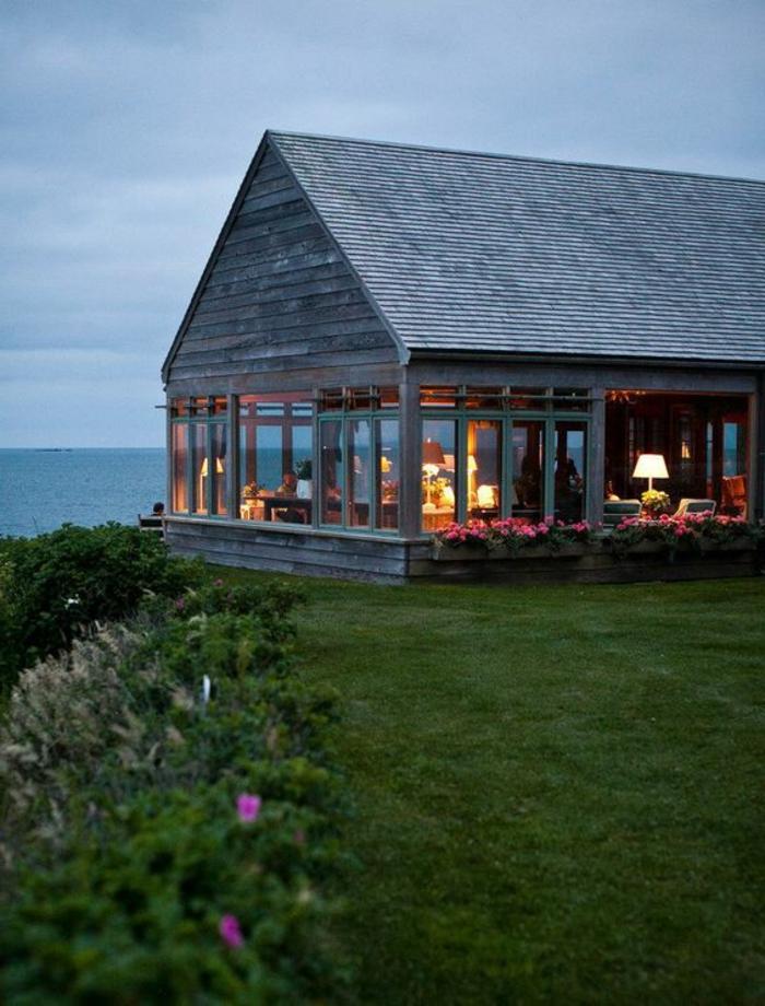 casa de campo, villa de madera y grandes ventanales en la orilla de un lago, césped y flores