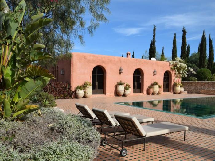 casa de campo, villa en color ladrillo, patio con piscina, sillones y macetas