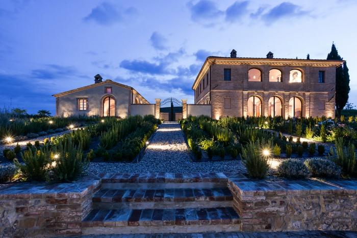 casa de campo, villa lujosa de piedra, jardín con senda de gravilla, cerca de metal