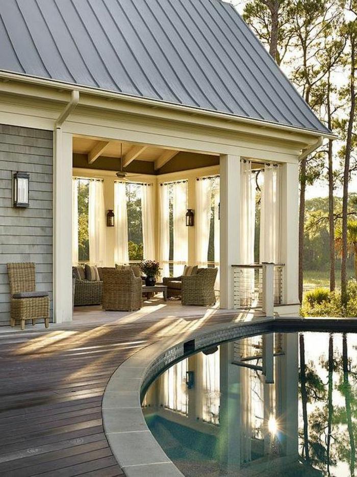 casa de campo, villa de madera y plñastico en blanco y gris, patio con sillones tejidos y piscina