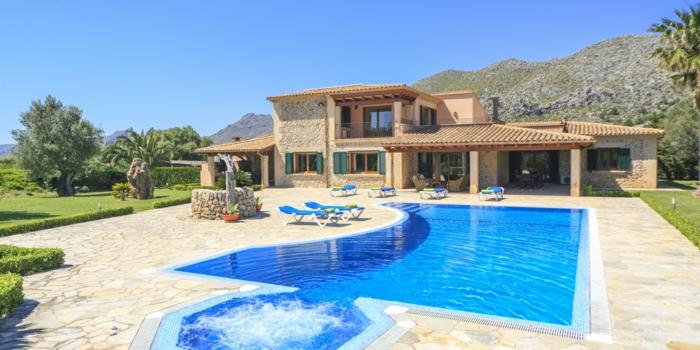 casa de campo, villa de piedra cerca de una colina , patio con césped, piscina y tumbonas