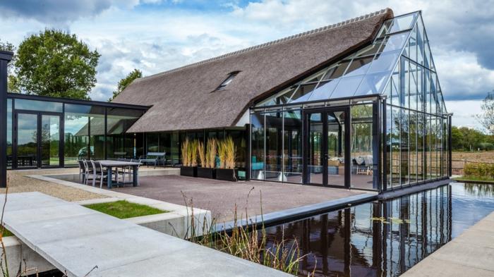 casa y campo, villa moderna de metal y vidrio, techo triangular, patio con lago artificial y mesa