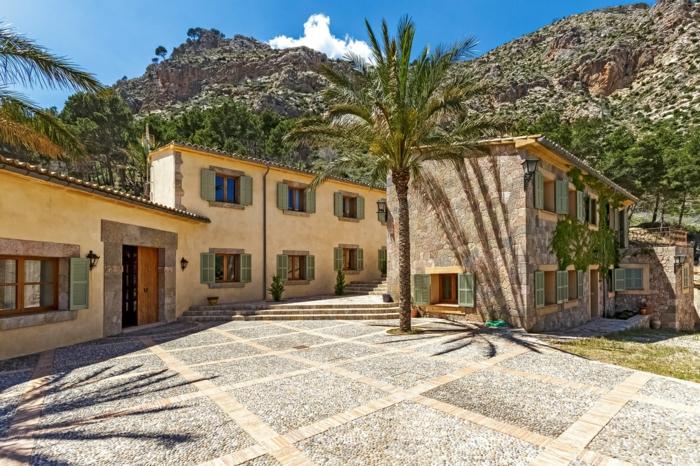 casa y campo, villa en color amarillo nápoles, contraventanas en azul, patio con palmeras, paisaje con montaña