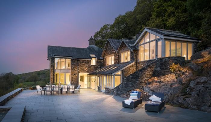 casa y campo, villa asimétrica de piedra con ventanalesm, patio con tumbona, mesa y escaleras