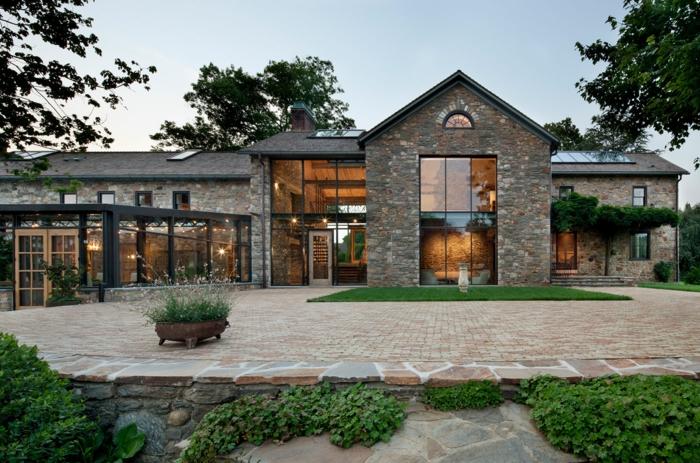 casa y campo, villa de piedra con ventanales, patio pavimentado y césped