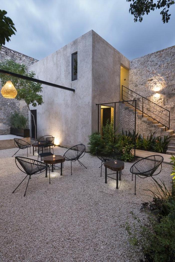 casas de campo, villa de concreto y piedra con patio, mesas y sillas de metal negro, ärboles y linterna