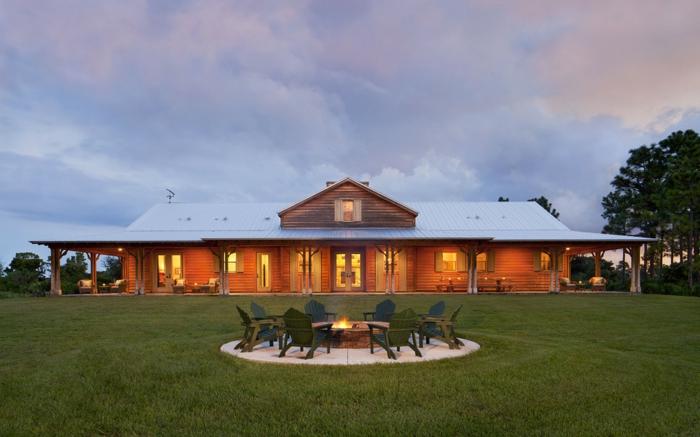 casas de campo, villa iluminada de un piso con techo triangular, patio con cesped y hogar rodeado de sillas