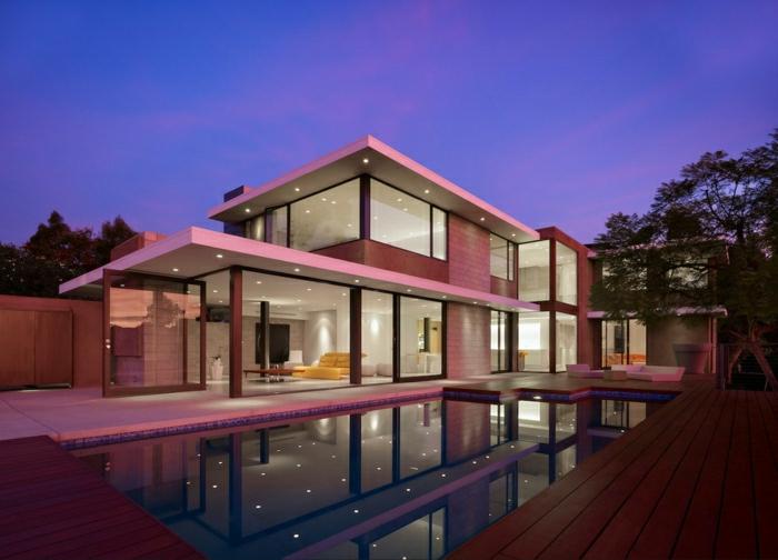 casas minimalistas. casa de dos pisos con piscina, iluminada de color rosa