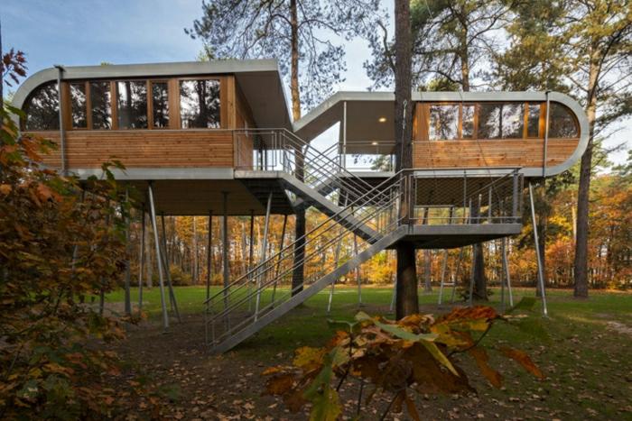fachadas de casas, dos casas de madera elevadas entre arboles, unidas por escaleras