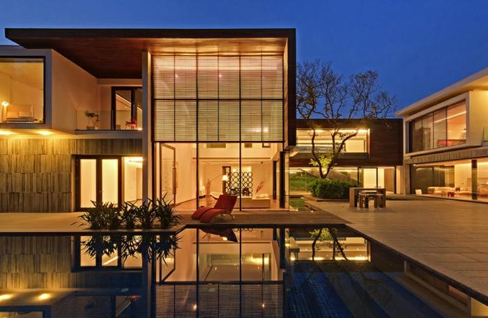 casas modernas, villa con estructura irregular y paredes de vidrio iluminada de noche, piscina