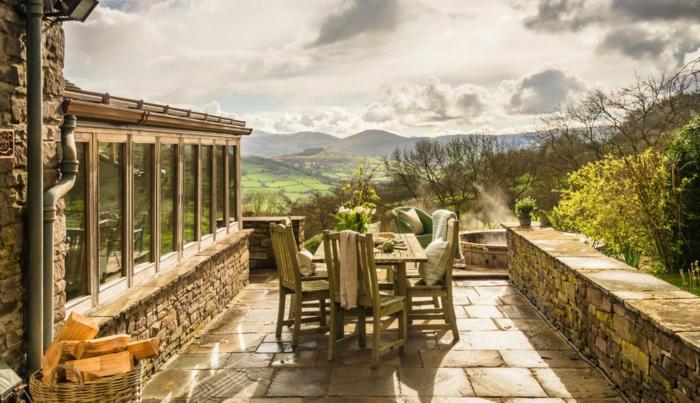 casas rurales baratas, casa con paisaje montañoso, patio de piedra con mesa, villa de piedra con ventanales