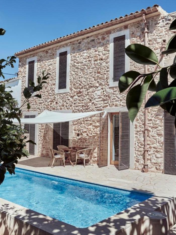 casas rurales baratas, villa de piedra con toldo y contraventanas, patio con piscina y mesa
