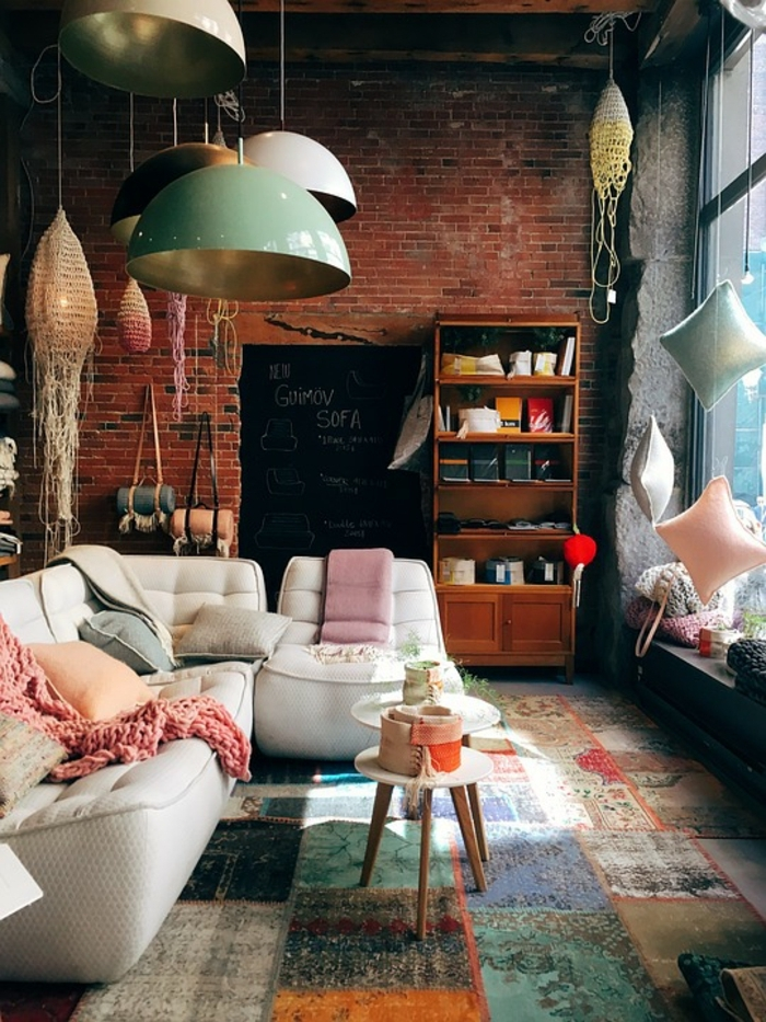 decoracion de interiores, pared de ladrillo, sofá con cojines, lámparas colgantes, estantería con libros, mesita redonda