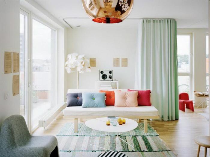 decoracion de interiores, sofá con cojines, mesa redonda, ventanal con cortinas, sillón y alfombra
