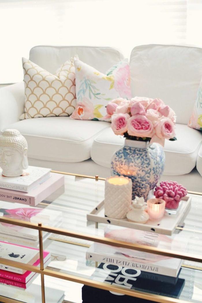 paredes pintadas, sofá blanco, mesa de vidrio, jarra con rosas, cojines y libros
