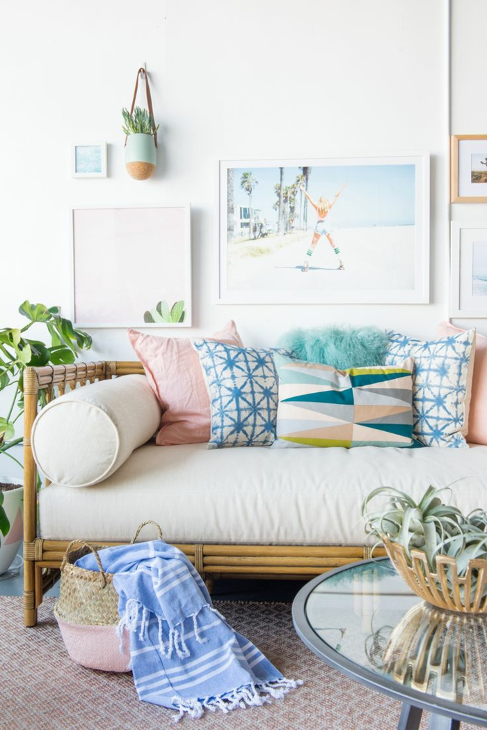 colores pastel, sofá con cojines de color, bolsa de rattan, mesa redonda de vidrio con planta