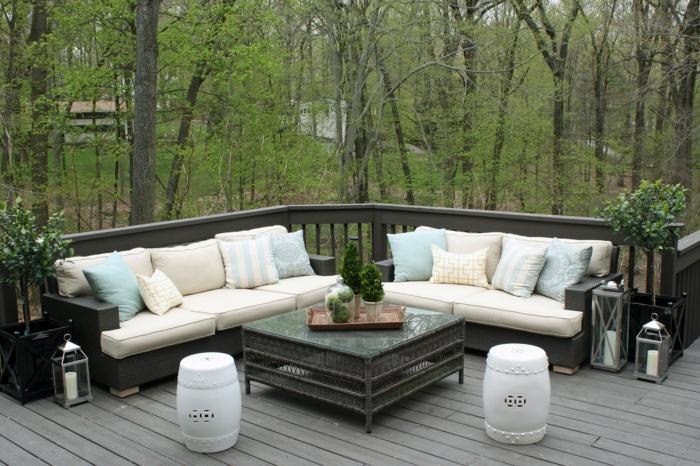 colores pastel, terraza de madera negra, dos sofás con cojines, mesa cuadrada de vidrio con plantas