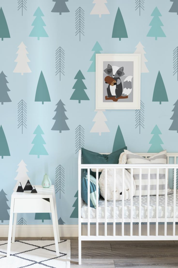 paredes pintadas, cama de bebé con cojines con caras, papel pintado de pinos, mesita blanca
