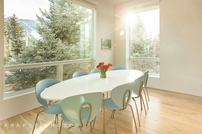 comedores modernos, mesa blanca ovalada, sillas azules, suelo laminado, flores, ventanales, pinos