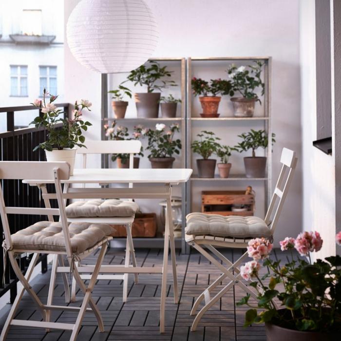 como decorar terrazas pequeñas, suelo de madera, mesa y sillas blancas, cojines y estantería con flores