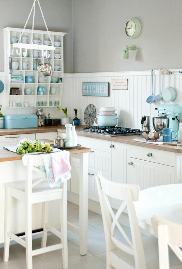 colores pastel, decoracion de cocina en azul y blanco, estantería con tazas, reloj de pared, mesa y cubiertos