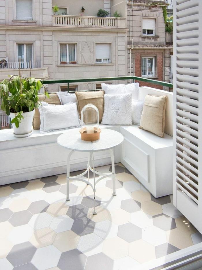como decorar una terraza pequeña, balcón en beige y blanco, mesa redonda, sofá con cojines y planta