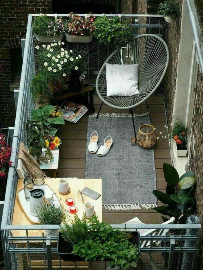 como decorar una terraza pequeña, balcón con tarima y silla Acapulco, mesa con vasos, revistas, plantas y flores