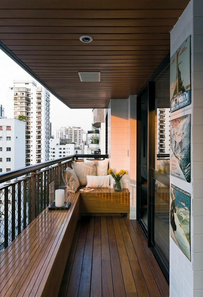como decorar una terraza pequeña, balcón con suelo tarima, banca con candela, cojines y flor, paisahe urbano