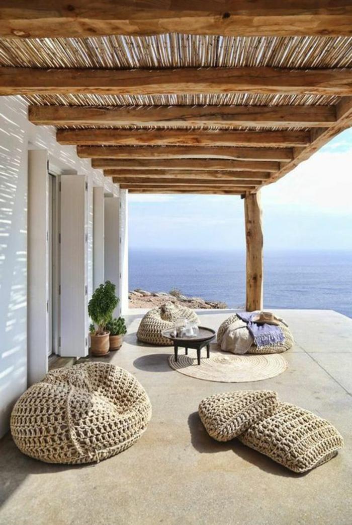 como decorar una terraza pequeña, terraza con suelo de cemento, pufs tejidos en beige, tapete de mimbre, paisaje de mar