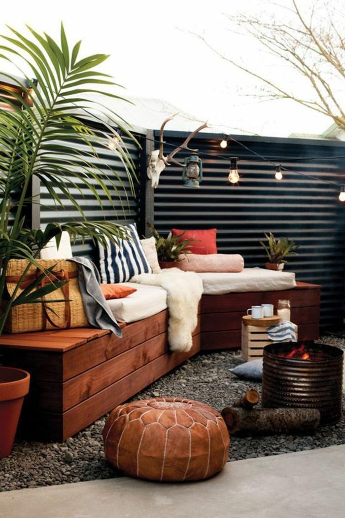 como decorar una terraza pequeña, terraza con suelo de gravilla, banca con cojines y cobija, fuego artificial