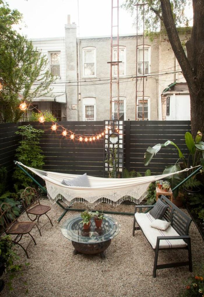 como decorar una terraza pequeña, terraza con hamaca blanca, mesa redonda de vidrio, suelo de gravilla, bombillas colgantes