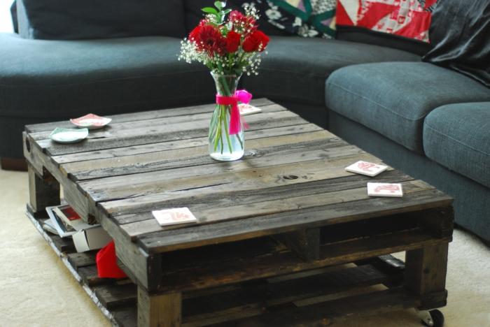 como hacer muebles con palets, mesa de palets madera oscura, jarra con rosas, sofá gris