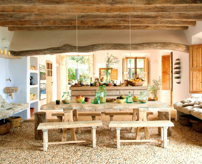 decoracion de comedores, comedor estilo rústico, mesa y bancas de madera clara, suelo de piedras, lámparas colgantes, sofá