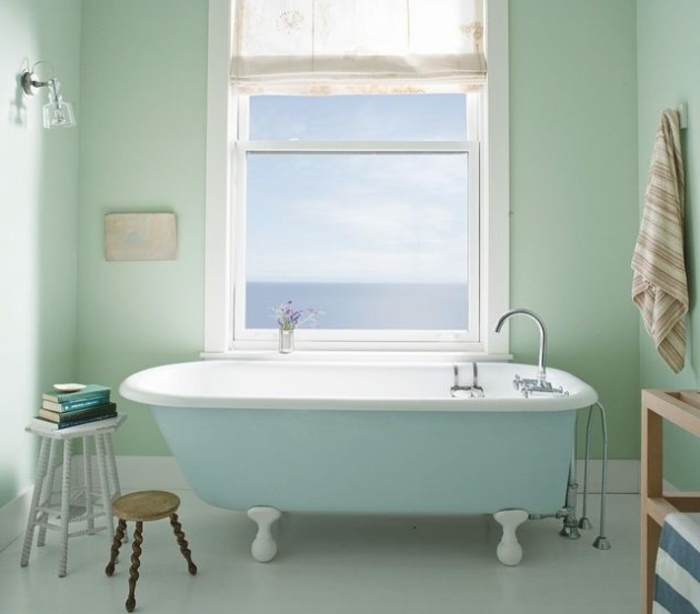 pintar paredes, baño decorado en verde y azul pastel, bañera con ventana, silla con libros